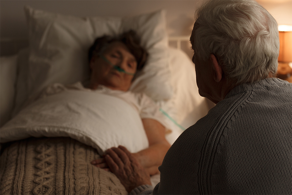 Man holding hand of bedridden elder.