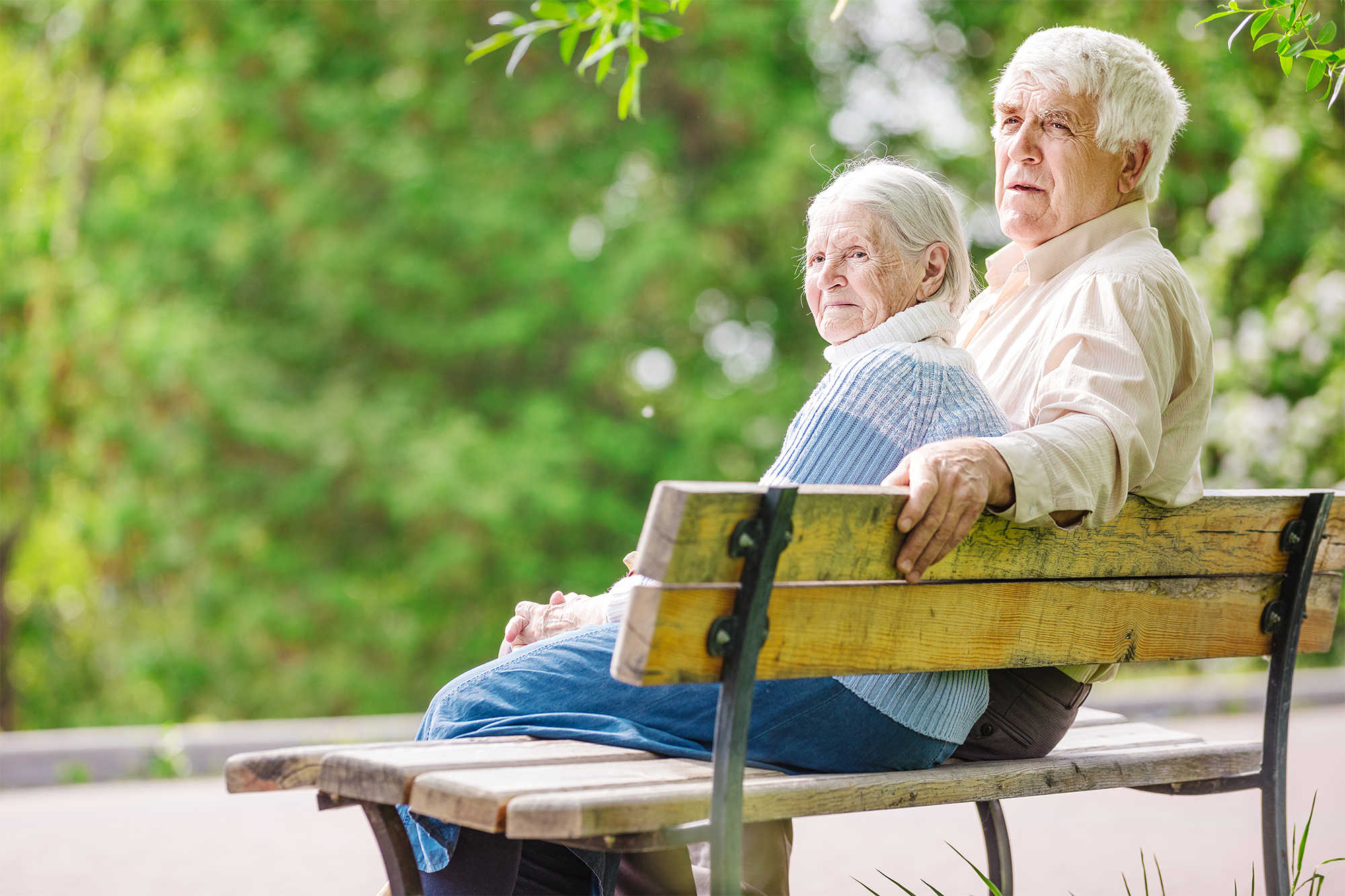 Two elders sitting together on sunny park bench.
