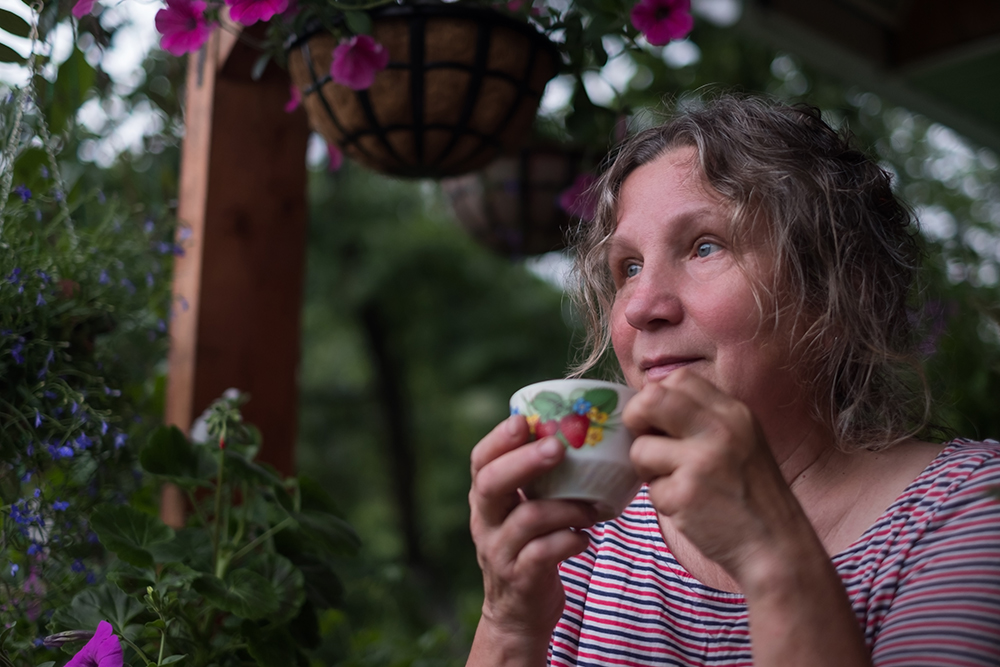 Woman sitting on a porch with planters and a warm beverage.